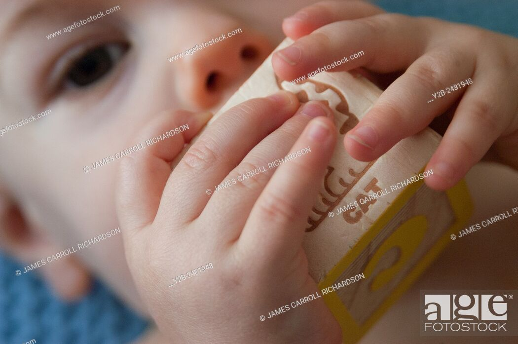 Stock Photo: Hands of baby playing with block.