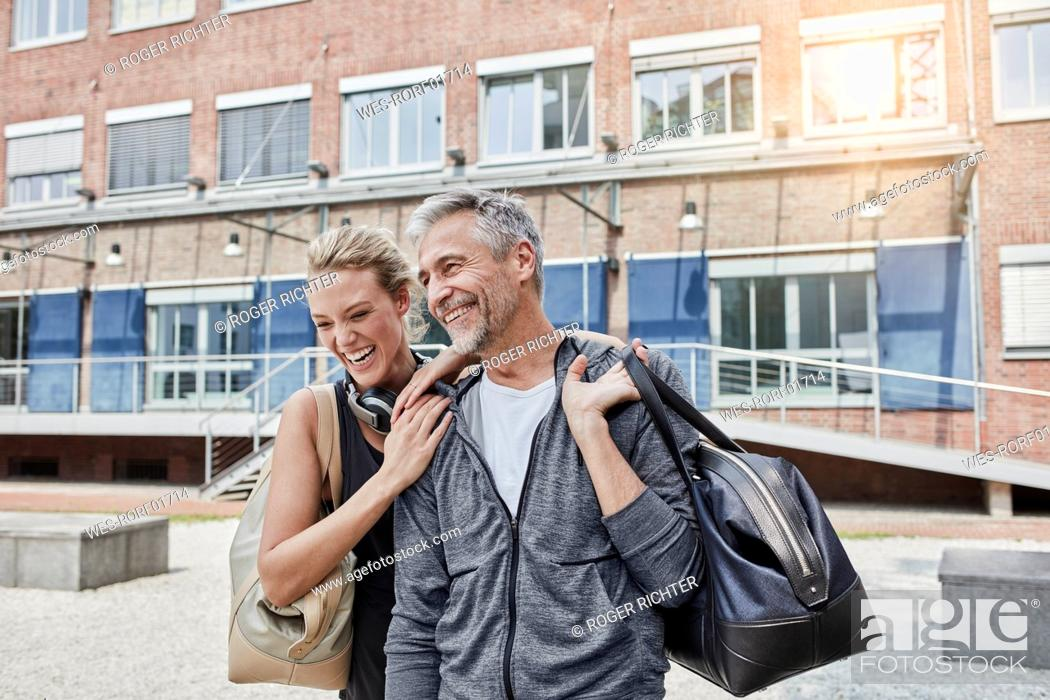 Stock Photo: Portrait of mature man and young woman with sports bag in front of gym.