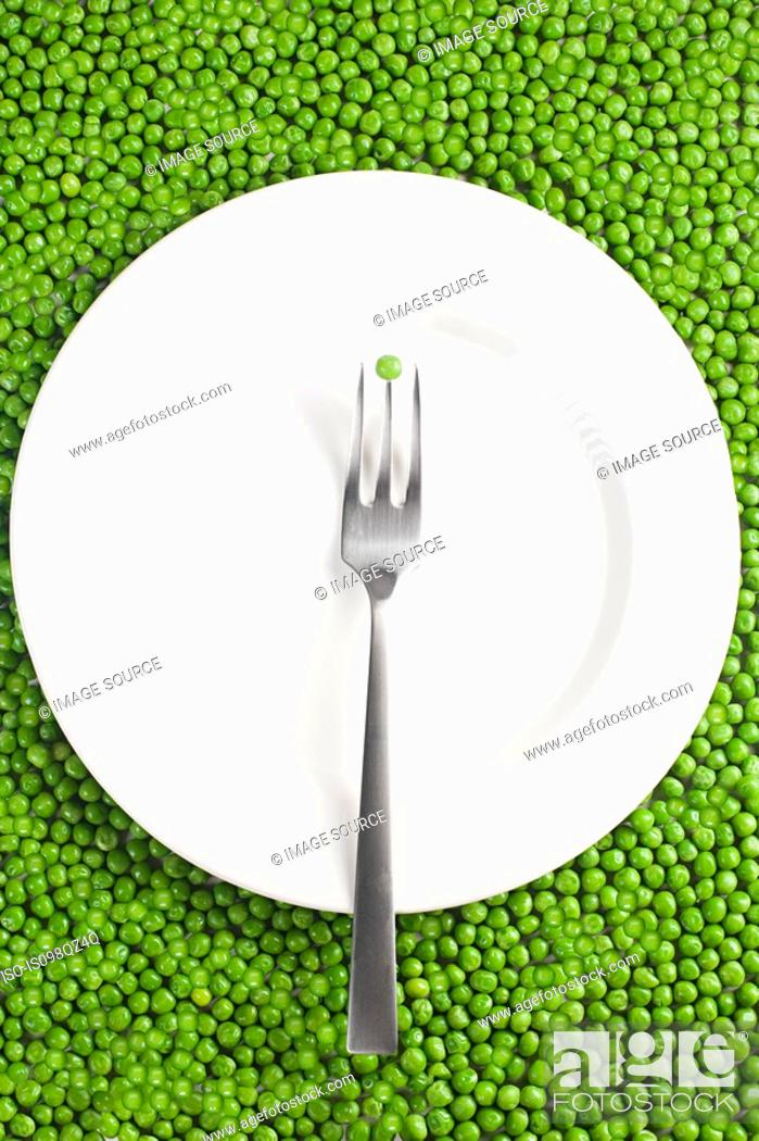 Stock Photo: Fork and plate on a pea background.