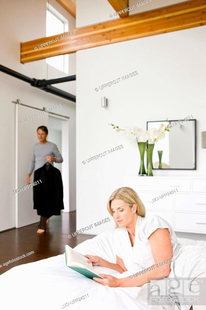 Stock Photo: Man holding suit and woman reading book in bedroom.