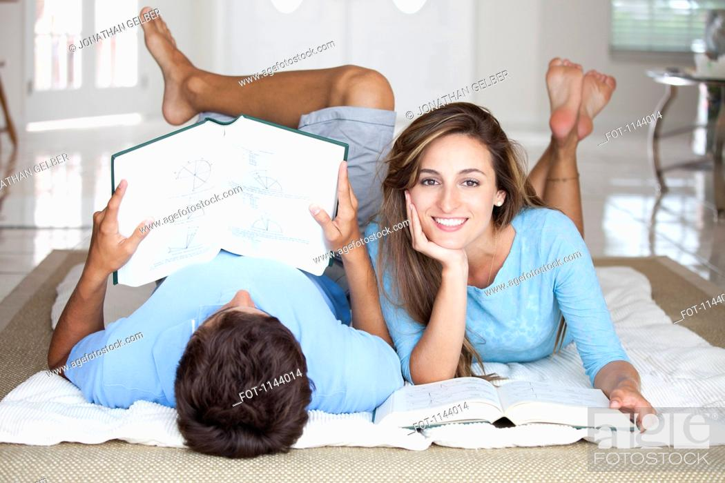 Stock Photo: A young couple lying on the floor studying with textbooks.