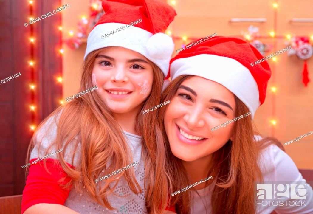 Stock Photo: .Closeup portrait of mother with cute little daughter wearing Santa hat baking on the kitchen at home, enjoying traditional Christmas preparation.