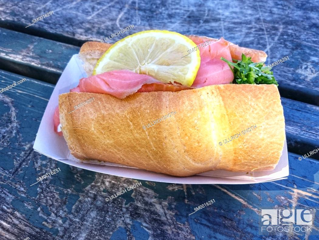 Photo de stock: Freshly prepared fish sandwich with salmon on a shabby wooden table.