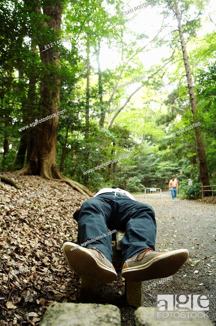 Stock Photo: Man sleeping in park, Tokyo, Japan.