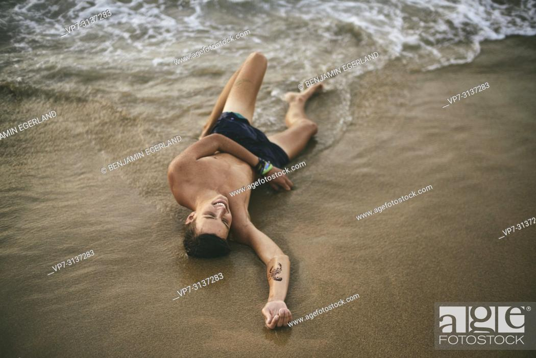 Photo de stock: Young man lying on Potamos beach, in holiday destination Malia, Crete, Greece.