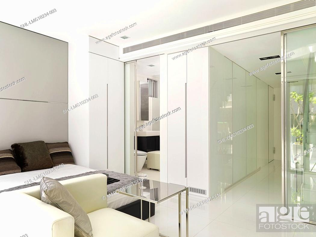 Stock Photo: Mostly white modern bedroom and bathroom.