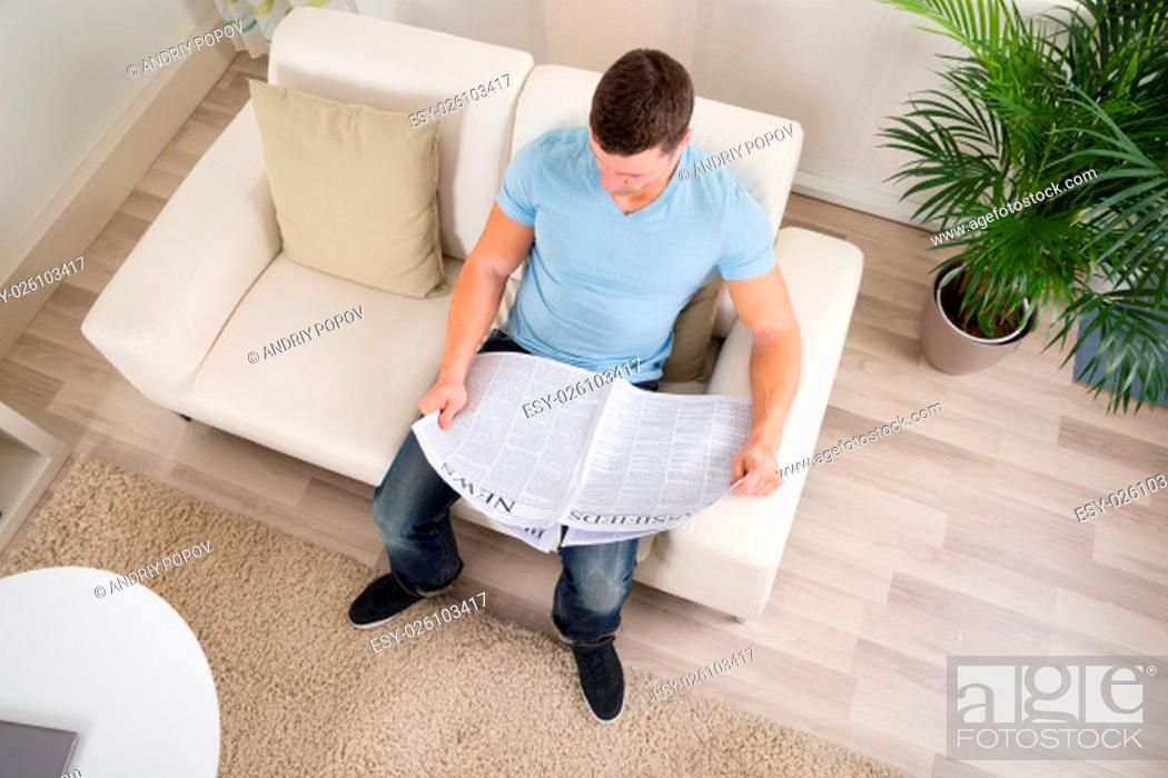 Stock Photo: High angle view of mid adult man reading newspaper on sofa at home.