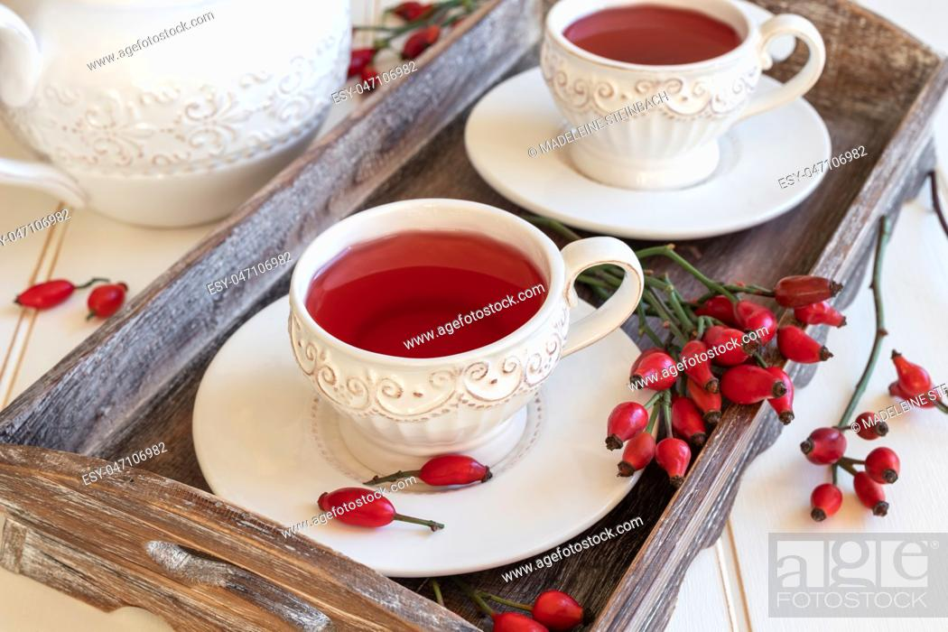 Stock Photo: Rose hip tea in white vintage cups.