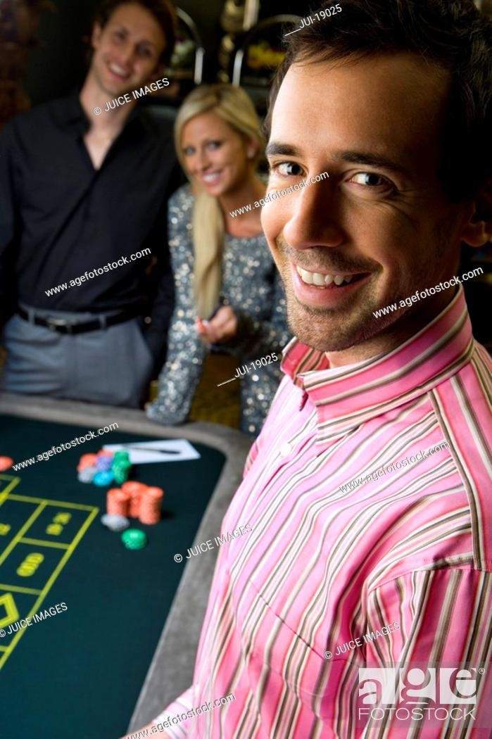 Stock Photo: Young man by friends gambling at roulette table, smiling, portrait, close-up.