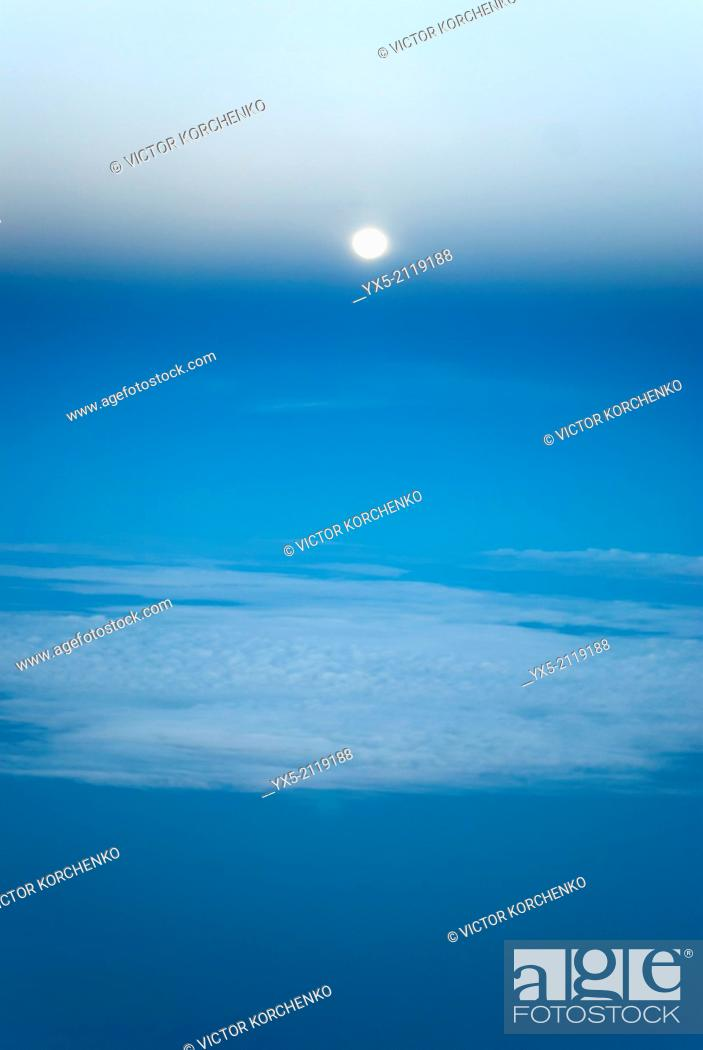 Stock Photo: Aerial view of the moon and clouds from an airplane.