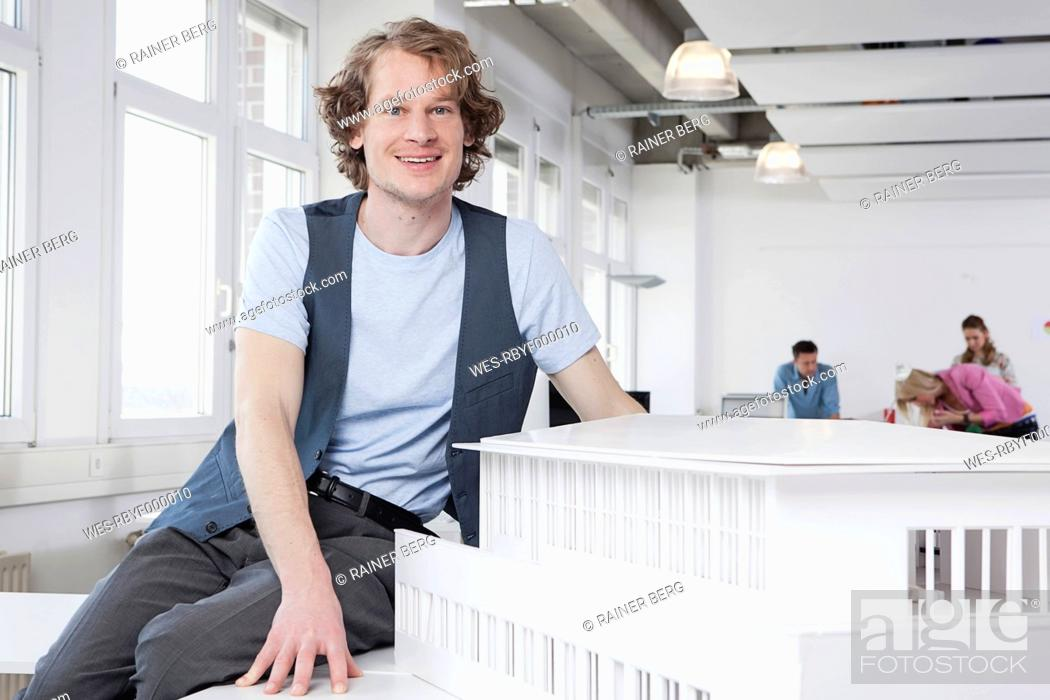 Stock Photo: Germany, Bavaria, Munich, Architect with architectural model, colleagues working in background.