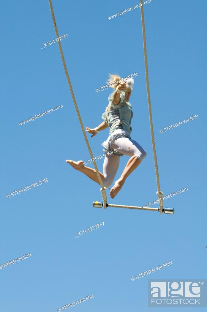 Stock Photo: Trapeze artist lets go of the swing.