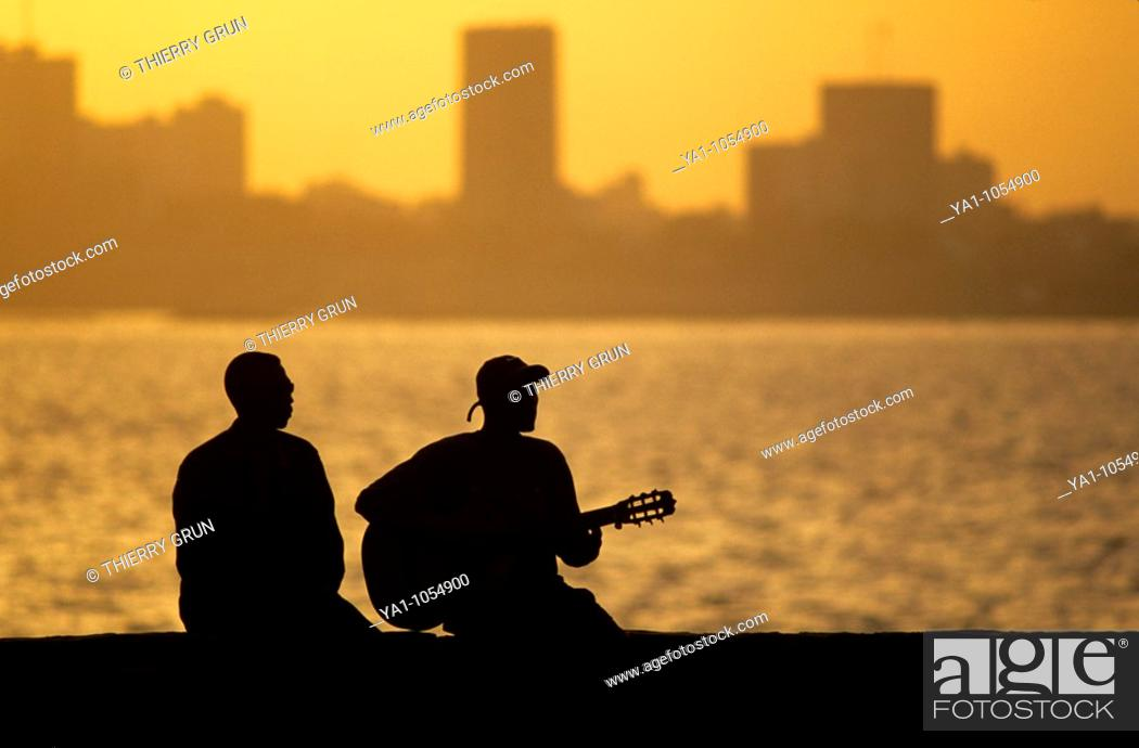 Stock Photo: Local musician playing blues music at Goree island during sunset. Background, capital city Dakar. Senegal, West Africa.