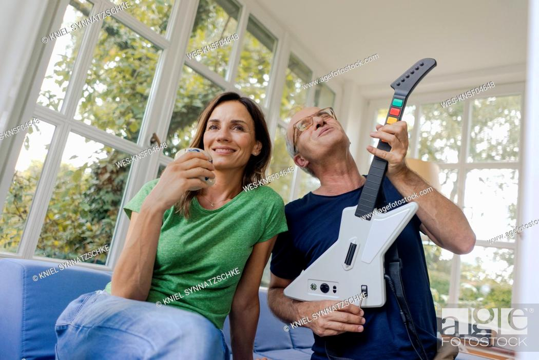 Imagen: Mature couple sitting on couch at home with man playing toy electric guitar.