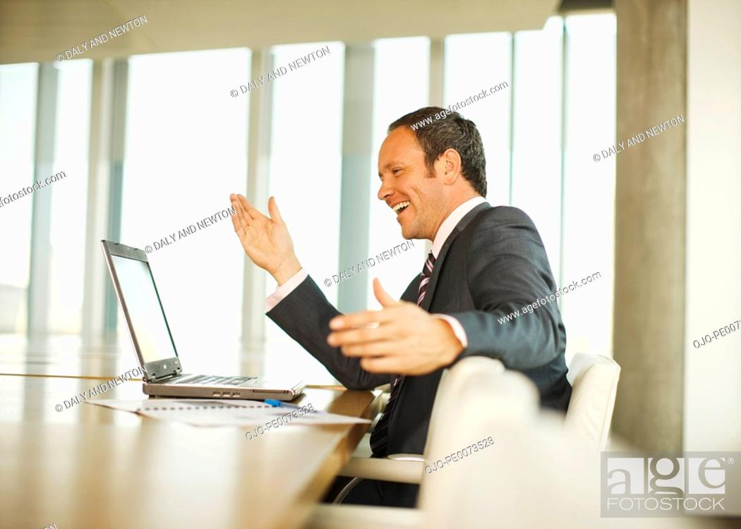 Stock Photo: Happy businesswoman looking at laptop and gesturing.