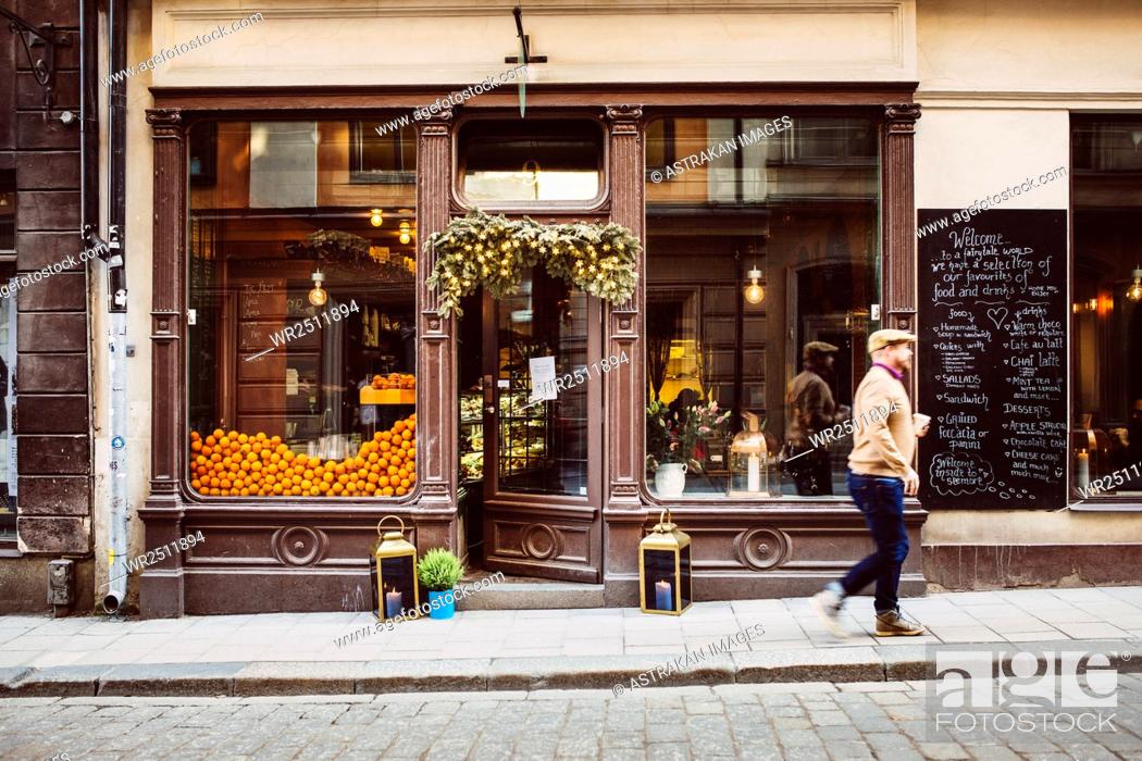 Stock Photo: Sweden, Stockholm, Gamla Stan, Man walking by cafe.
