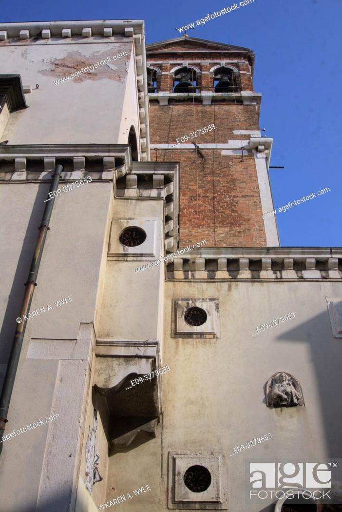 Stock Photo: architectural contrast, brick church tower behind very different building with odd round windows set in squares and one wall sculpture showing, Venice, Italy.
