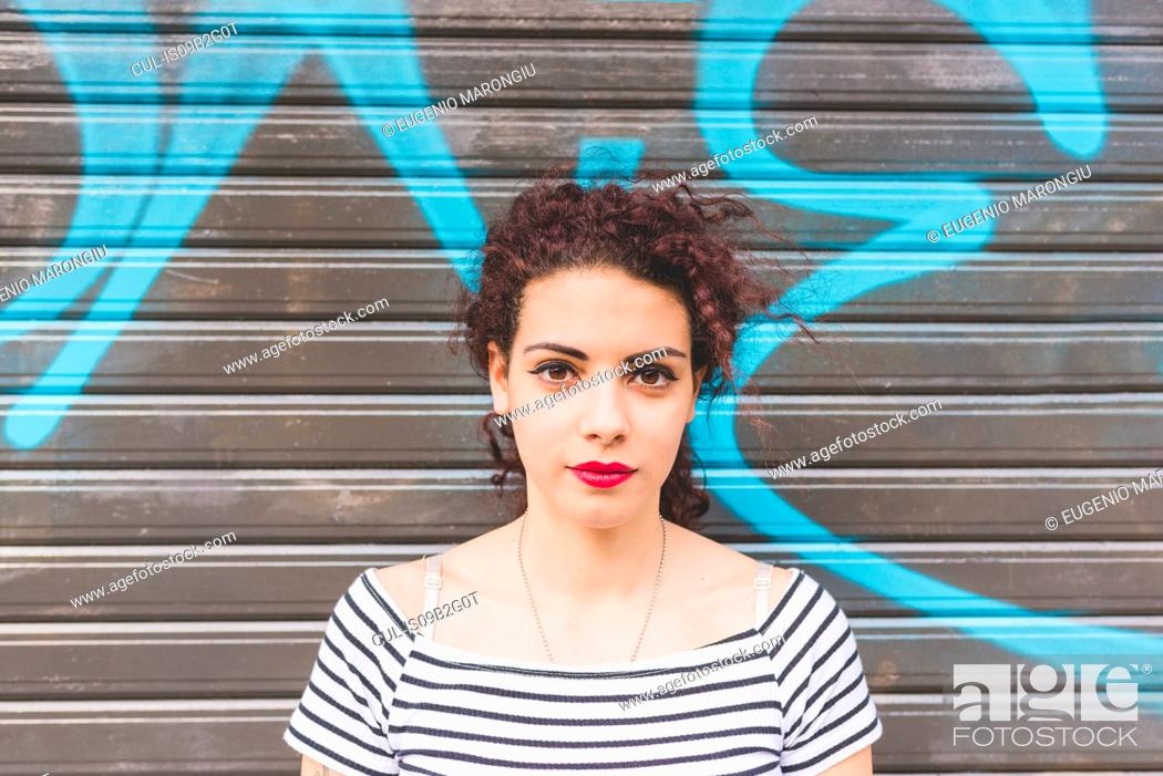 Stock Photo: Portrait of woman in front of graffiti shutter.
