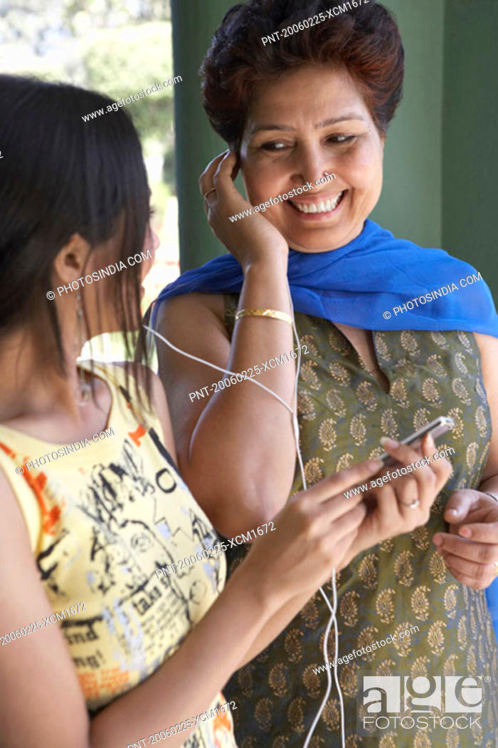 Stock Photo: Close-up of a mother and her daughter listening to an MP3 player.