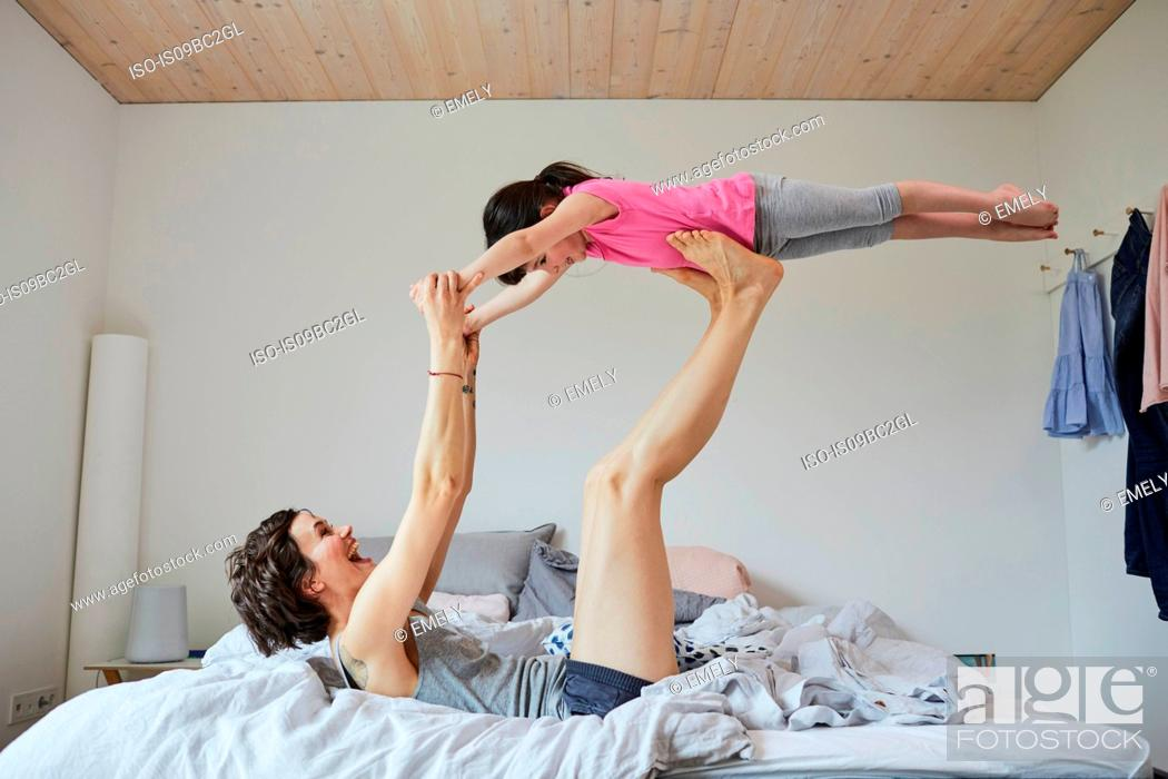 Stock Photo: Mother and daughter playing in bedroom, mother balancing daughter on feet.