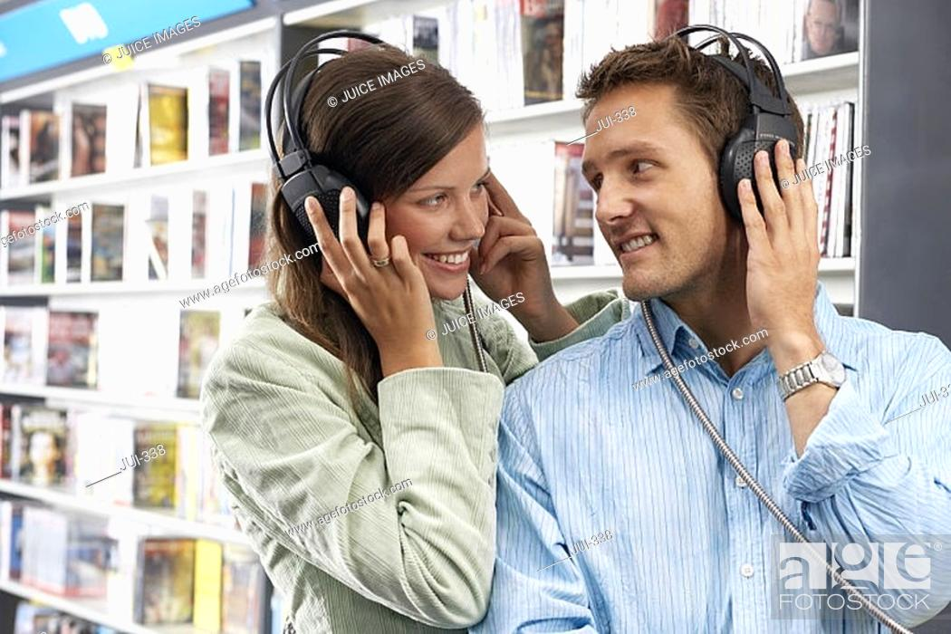 Stock Photo: Young couple wearing headphones, listening to CDs in record shop, smiling.