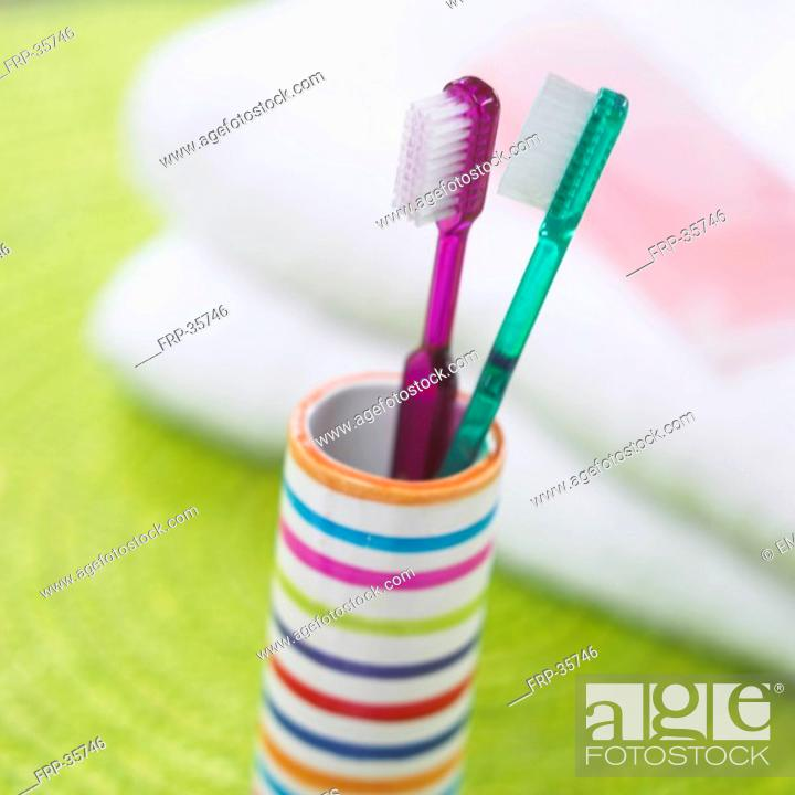 Stock Photo: two toothbrushes in a striped beaker.