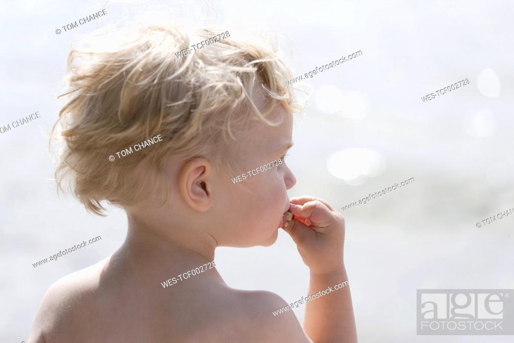 Stock Photo: Germany, Bavaria, Boy eating bread, close up.