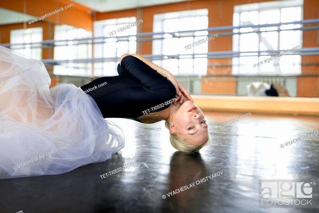 Stock Photo: Ballet dancer practicing on studio floor.