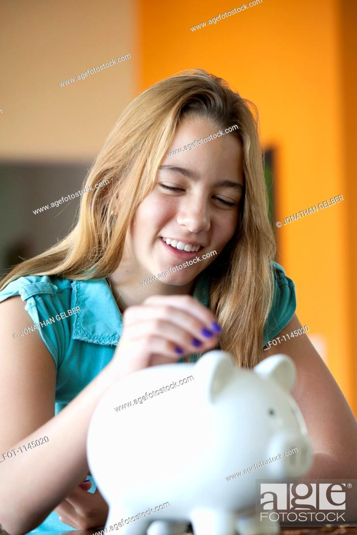 Stock Photo: Girl putting coin in piggy bank.