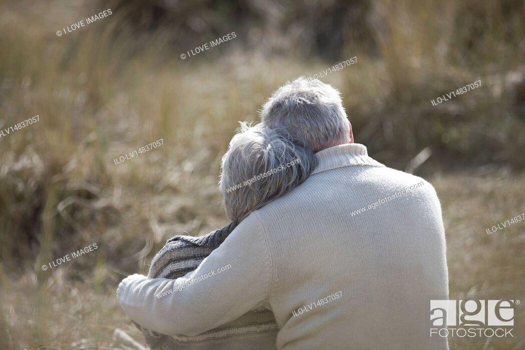 Stock Photo: A senior couple sitting amongst the sand dunes, embracing.