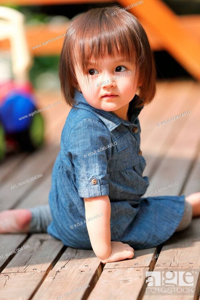 Stock Photo: Mixed-race young girl playing on wooden deck.
