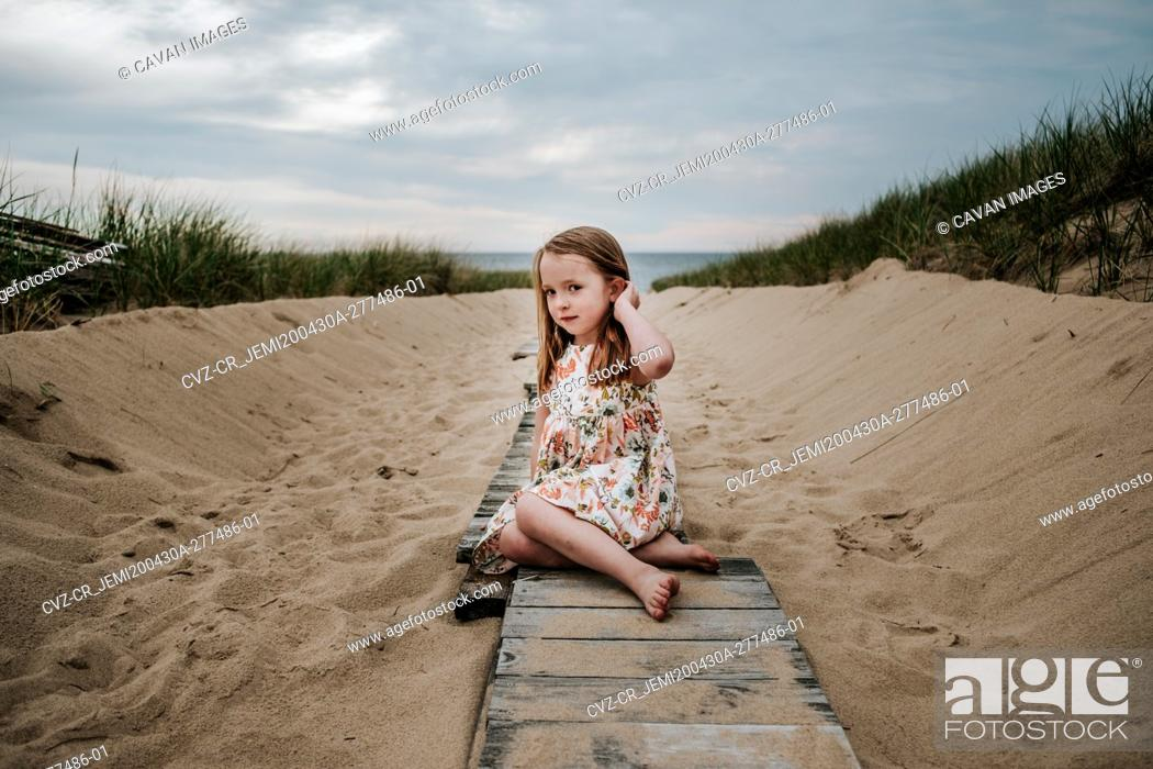 Stock Photo: young girl sitting on private board walk going out to lake.