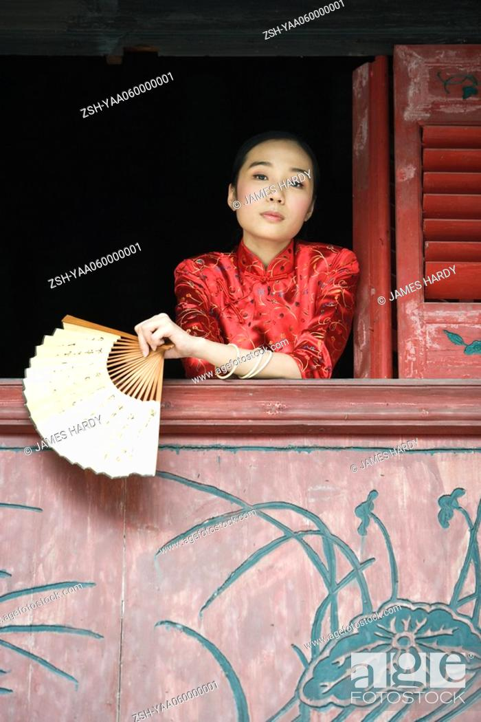 Stock Photo: Young woman dressed in traditional Chinese clothing, leaning out of window sill, holding fan.