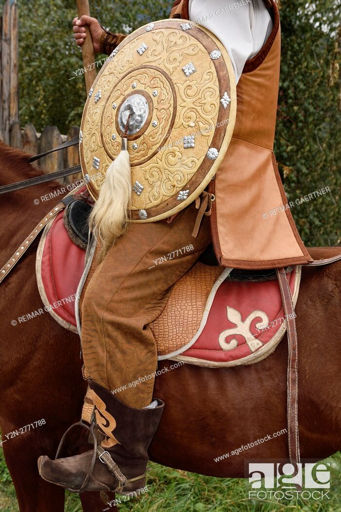 Stock Photo: Detail of guard in traditional hun clothes with shield and spear on horseback Kazakhstan.