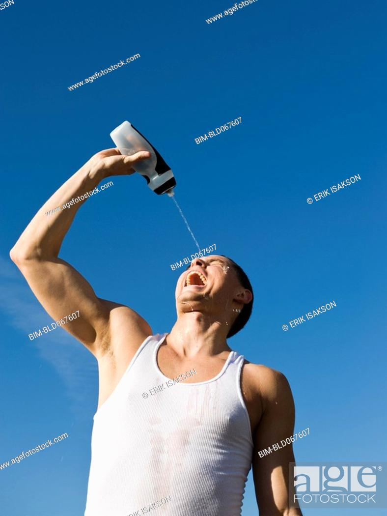 Stock Photo: African man squirting water on his face.