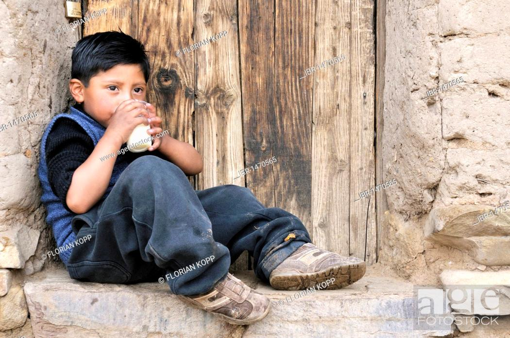 Stock Photo: A boy leaning against a wall with a glass of milk, Bolivian Altiplano highlands, Departamento Oruro, Bolivia, South America.