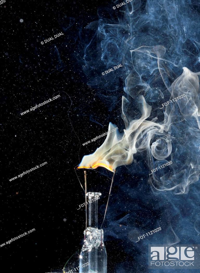 Stock Photo: A light bulb filament on fire.
