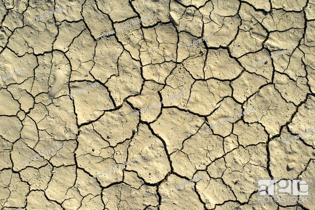 Stock Photo: Cracked soil texture. Hard shadows and sun. Dried ground. Pattern of many cracks for background.