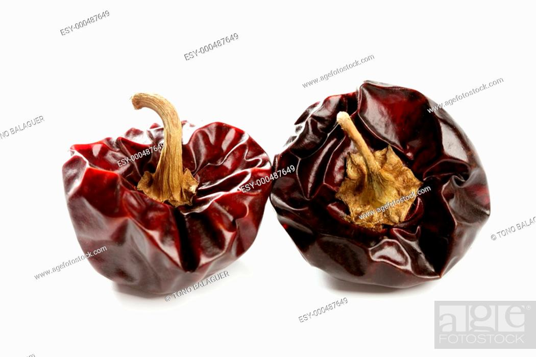 Photo de stock: Two round Mediterranean dried dark red peppers over white at studio, isolated.