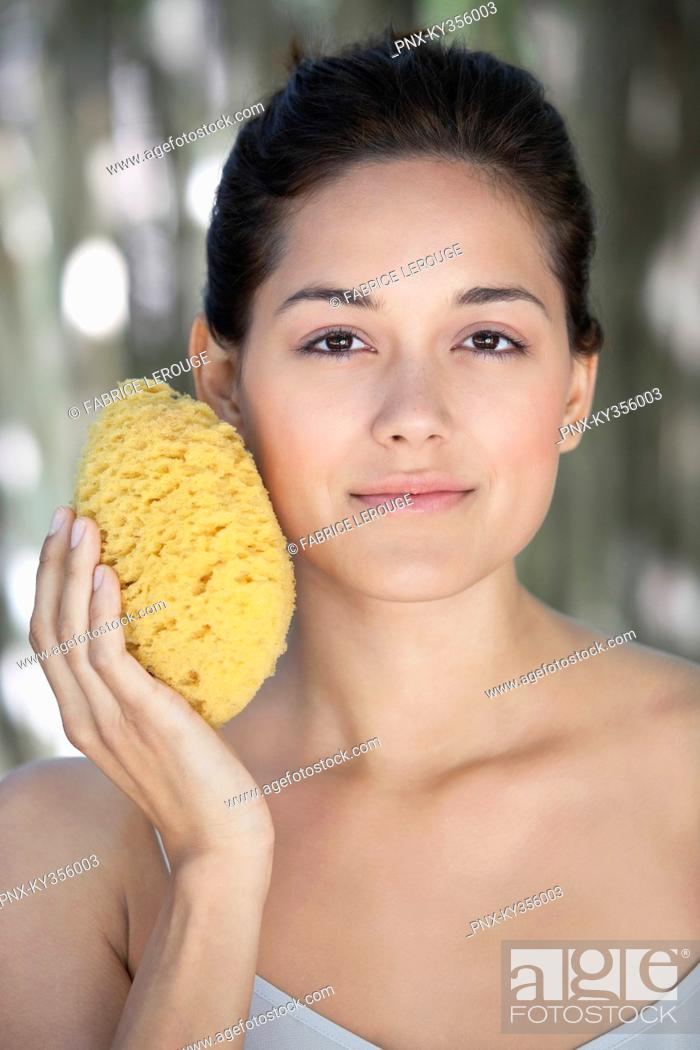 Stock Photo: Beautiful young woman holding a bath sponge on her face.
