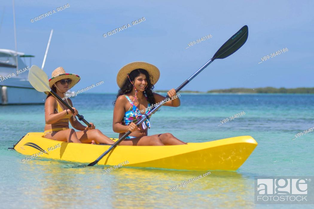 Stock Photo: Two young Hispanic women paddling in yellow kayak at summer travel destination. Exotic Caribbean beach with turquoise water sea.