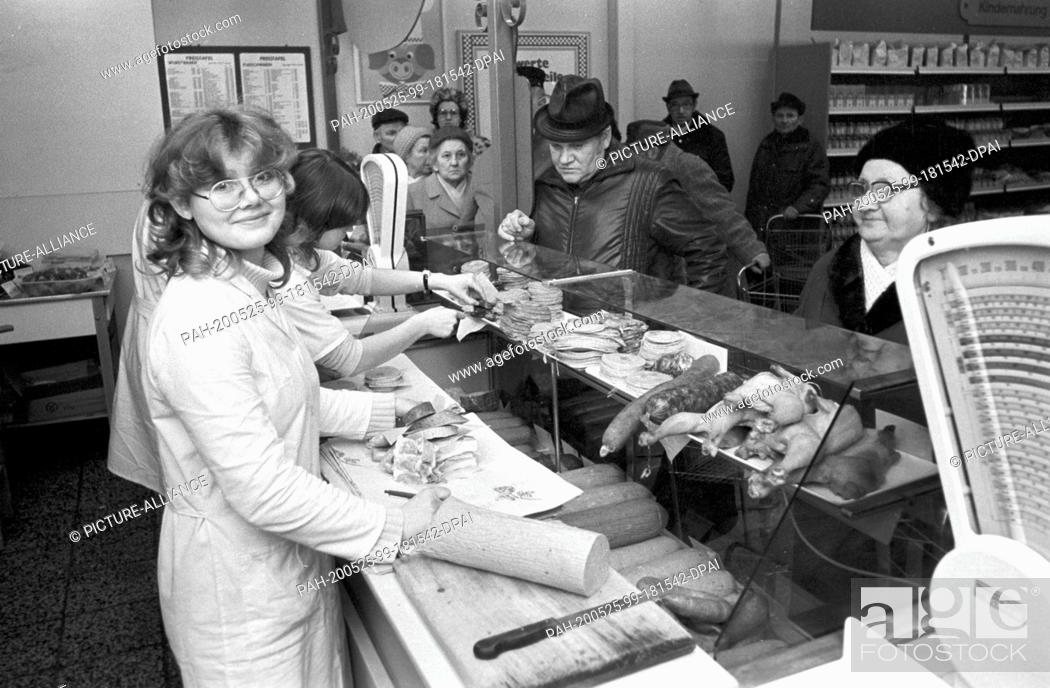 Stock Photo: 30 November 1984, Saxony, Torgau: In a department store in Torgau in the mid-1980s, sales assistants offer fresh produce at the meat stall / sausage counter.