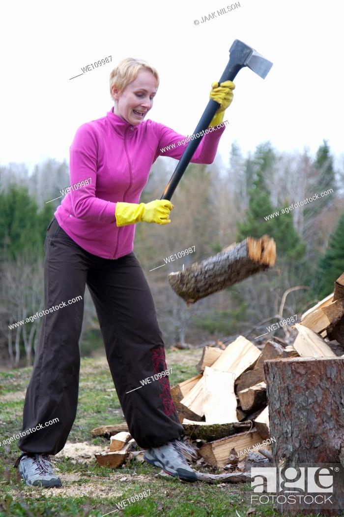 Stock Photo: Caucasian Woman Slipping and Chopping Firewood Using Axe.