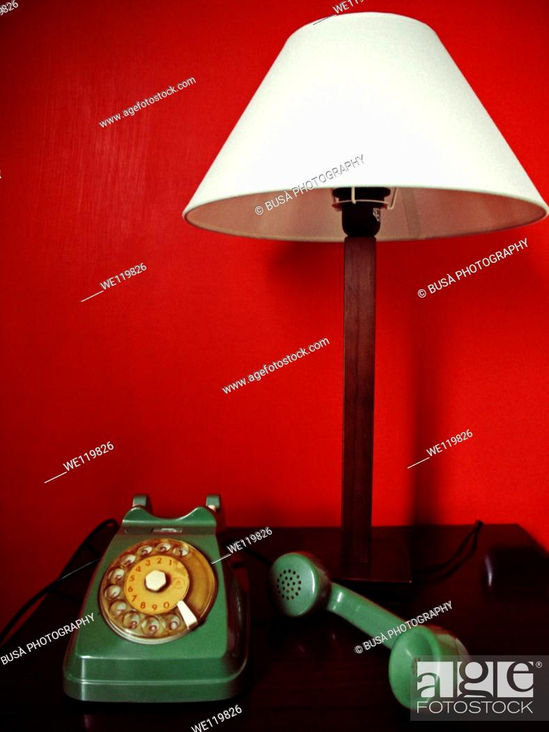 Stock Photo: Green vintage telephone on a red background.