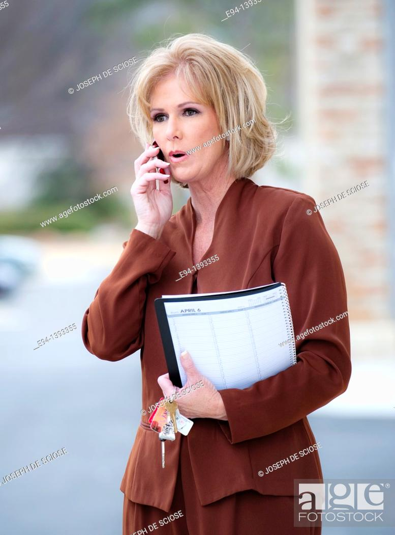 Stock Photo: Fifty year old blond woman in business attire talking on a mobile phone.