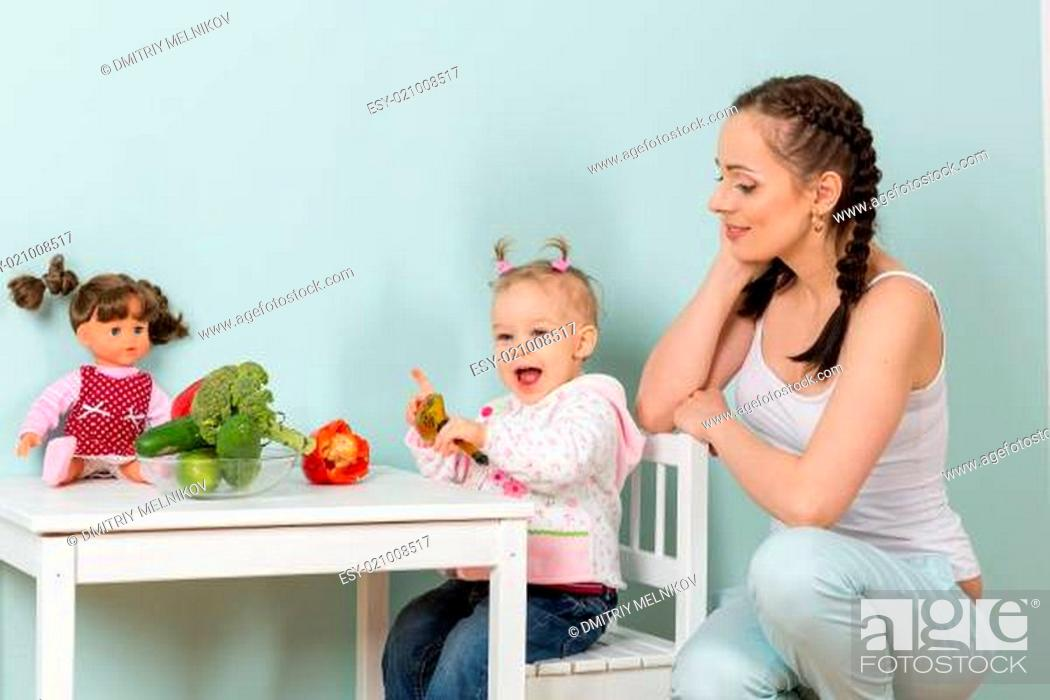 Stock Photo: Mother with baby in kitchen.
