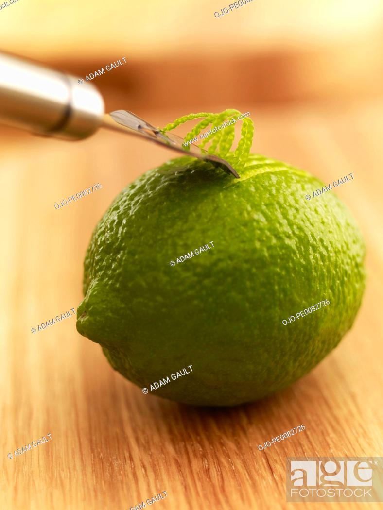 Stock Photo: Close up of zester peeling lime.