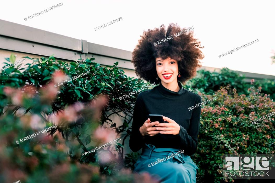 Stock Photo: Happy young woman outdoors with mobile phone.