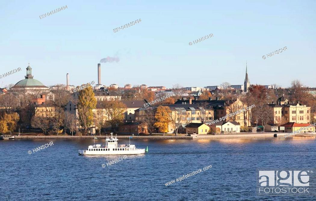 Stock Photo: The beautiful Skeppsholmen and a ferry in central Stockholm during the autumn. Sea, houses and trees.