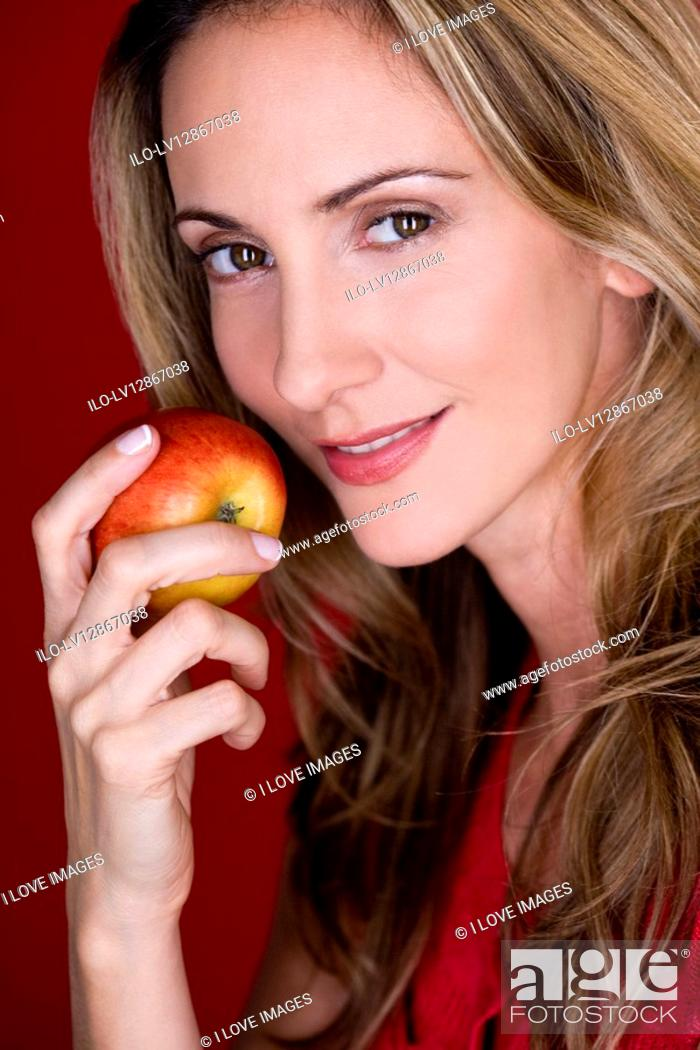 Stock Photo: A mid adult woman eating an apple.